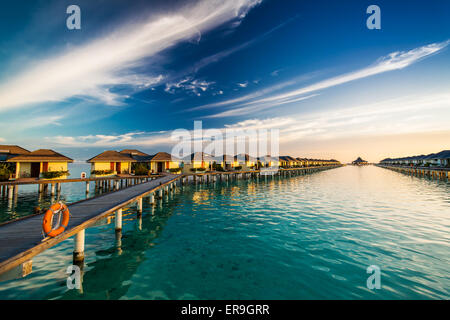Sunset time on island of Maldives over the bridge connecting over-water bungallows - Stock Photo