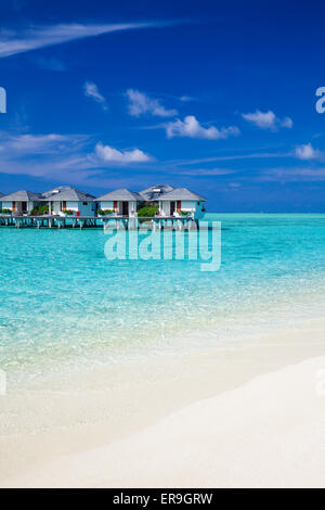 Water villas in the tropical ocean and white sandy beach - Stock Photo