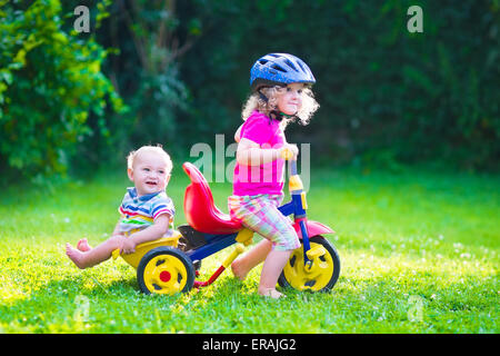 Children riding a bike. Kids enjoying a bicycle ride. Little preschooler girl and baby boy, brother and sister - Stock Photo