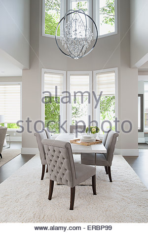 Vaulted ceiling chandelier hanging over elegant dining table - Stock Photo
