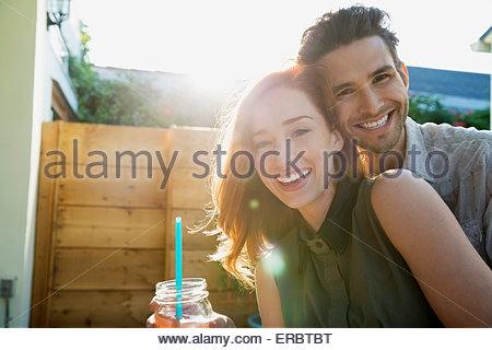 Portrait smiling couple drinking cocktail on sunny patio - Stock Photo