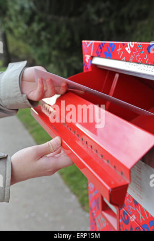 Hand sending a tax report letter in a red mail box - Stock Photo