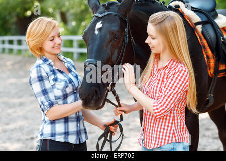 Happy sisters  standing with the horse - Stock Photo