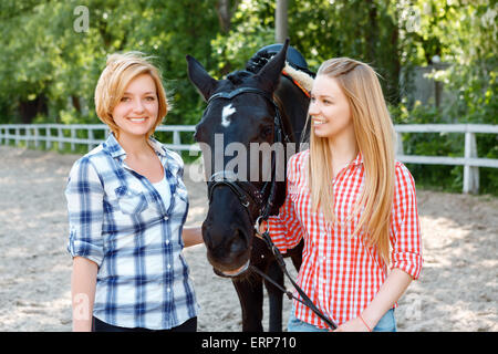 Girls standing alongside with the horse - Stock Photo
