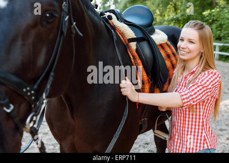 Girl standing near the horse - Stock Photo