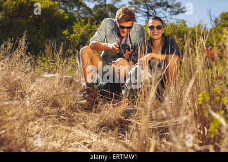 Outdoor shot of young couple on hiking trip taking a break. Woman smiling while man looking at his camera. - Stock Photo
