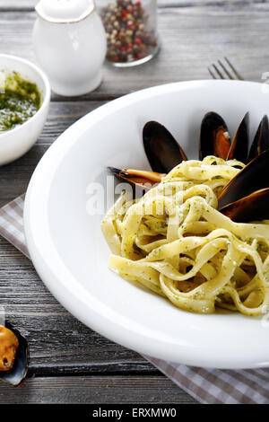 Pasta with mussels on a plate, food - Stock Photo