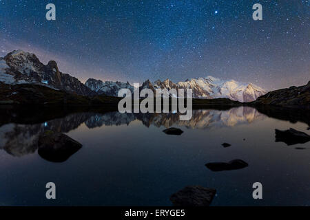Starry sky with Milky Way and Mont Blanc massif reflected in the Lac des Chésery, Chamonix, Rhone-Alpes, France - Stock Photo