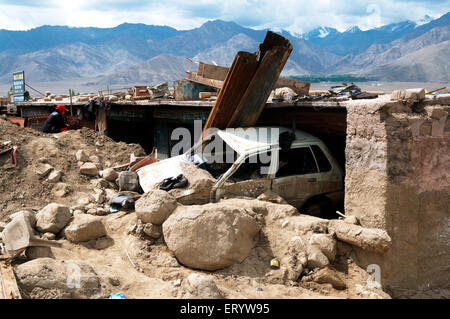 Damaged car stuck in mud at choglamsar due to flashflood ; Leh ; Ladakh ; Jammu and Kashmir ; India - Stock Photo