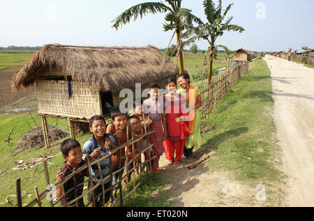 Children in front of bamboo cottages at majuli island Assam India - Stock Photo