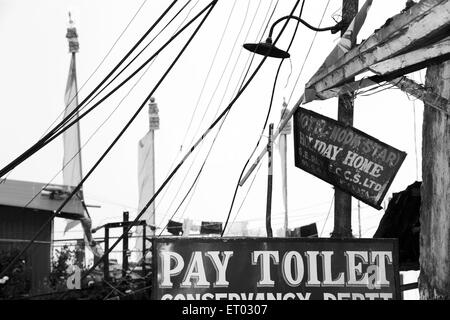 Wires hanging and pay toilet sign and Buddhist prayer flags , Darjeeling , West Bengal India , 2011 - Stock Photo
