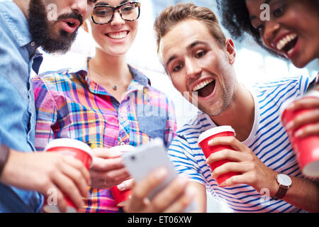 Friends laughing and drinking coffee around cell phone - Stock Photo