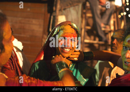 Haldi or turmeric being smeared on face of woman ; wedding of eunuchs on occasion of Bewa Purnima at Ghatkopar ; - Stock Photo