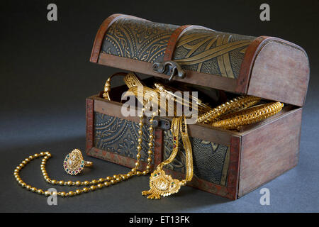 Wooden Jewellery box with Gold Bangles Necklace and Ring - Stock Photo