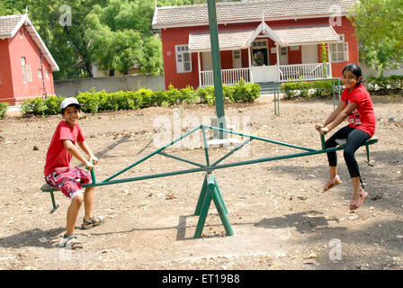 Young girl and boy playing on seesaw in front of house - Model Release # 152 - Stock Photo