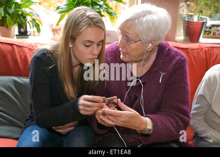 Grandmother asking her granddaughter about how to use an i-pod and listen to music because she does not understand - Stock Photo