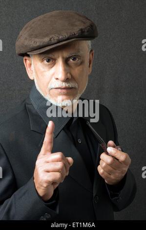 Portrait of maharashtrian elderly man holding smoking pipe in left hand Pune Maharashtra India MR # 686P - Stock Photo