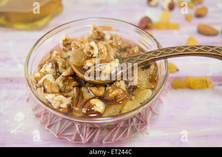 Walnuts hazelnuts and honey in a glass dish with a vintage wooden spoon on a pink tablecloth - Stock Photo