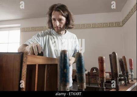 Carpenter French polishing wooden drawer at workshop, Bavaria, Germany - Stock Photo