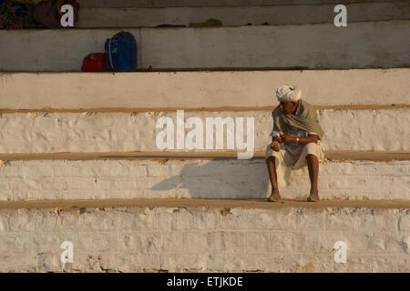 Rajasthani man in traditional style attire on the stadium steps. Pushkar, Rajasthan, India - Stock Photo