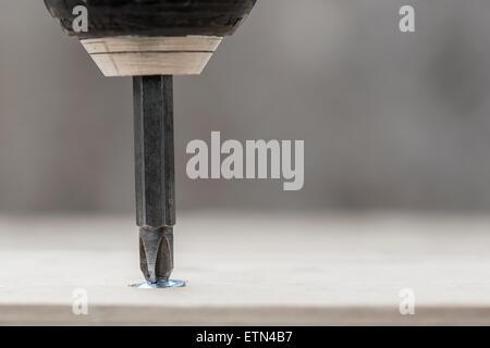 Screwing screw into wooden plank, closeup - Stock Photo