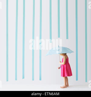Girl with an umbrella standing under rain made of stripes - Stock Photo