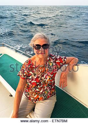 Portrait of a senior woman sitting on boat, Maldives - Stock Photo