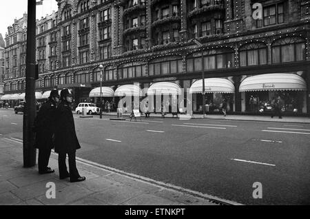 Police in two's keep an eye on Harrods as the last minute shoppers get Christmas presents in, London. 23rd December - Stock Photo