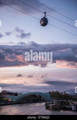 Aerial tramway passing over old part of Tbilisi, capital of Georgia. Bridge of Peace seen on background - Stock Photo