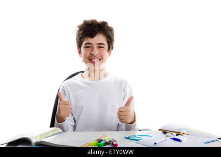 Caucasian latin young boy sits in front of homework, smiles  and feels happy  showing success thumbs up sign with - Stock Photo