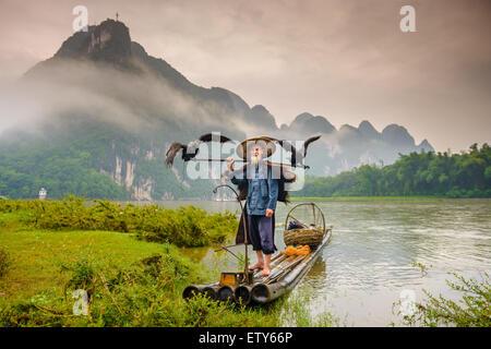 Cormorant fisherman and his birds on the Li River in Yangshuo, Guangxi, China. - Stock Photo