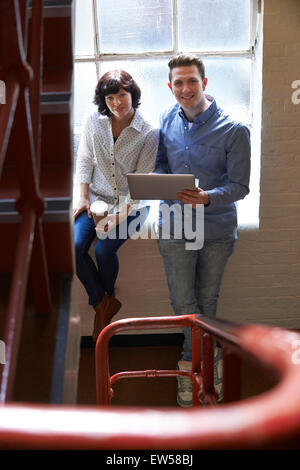 Two Businesspeople Having Informal Meeting On Office Stairs - Stock Photo