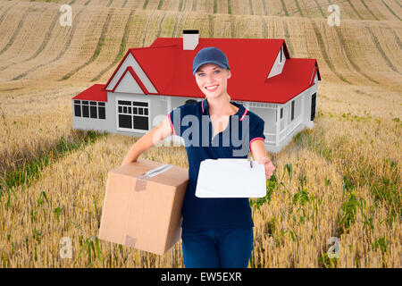 Composite image of happy delivery woman holding cardboard box and clipboard - Stock Photo
