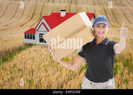 Composite image of happy delivery woman holding cardboard box - Stock Photo