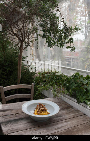 Dish of egg pasta on a wooden table in an Italian restaurant. - Stock Photo