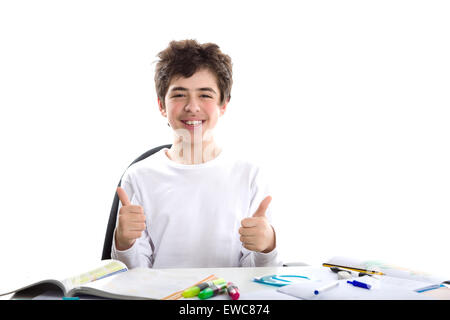 Caucasian smooth-skinned boy sits in front of homework, smiles  and feels happy  showing success thumbs up sign - Stock Photo