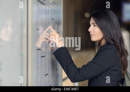 Attractive woman reading the train timetable running down the columns with her finger as she tries to find the right - Stock Photo