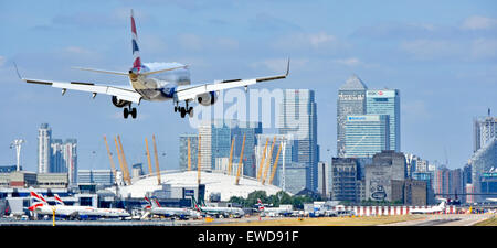 British Airways flight landing at London City Airport Newham with O2 arena & Canary Wharf skyline Tower Hamlets - Stock Photo