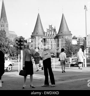 Ein Paar vor dem Holstentor in Lübeck, Deutschland 1960er Jahre. A couple in front of the Holstentor gate at Luebeck, - Stock Photo