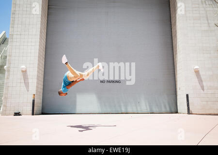 Young man somersaulting on street parcour parkour free running - Stock Photo