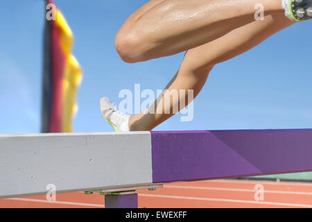 Female hurdle runner leaps over the hurdle. In the blurred background there  is a flag with german national colors - Stock Photo