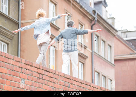 Rear view of middle-aged couple with arms outstretched walking on brick wall - Stock Photo