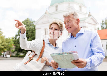 Middle-aged woman showing something to man holding map outdoors - Stock Photo