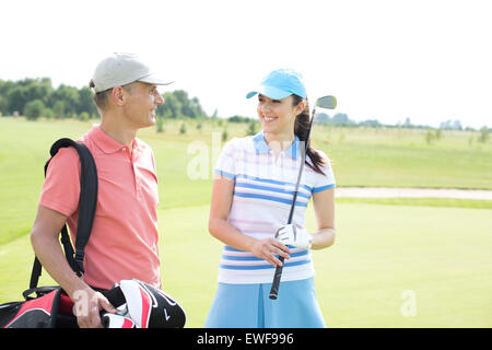 Happy male and female golfers communicating at course - Stock Photo