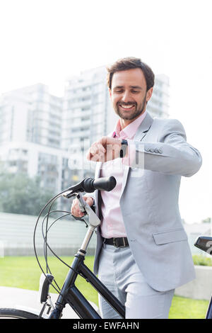 Happy businessman with bicycle checking time outdoors - Stock Photo