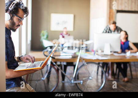 Casual businessman with headphones using laptop in office - Stock Photo