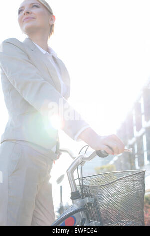 Low angle view of businesswoman standing with bicycle on sunny day - Stock Photo