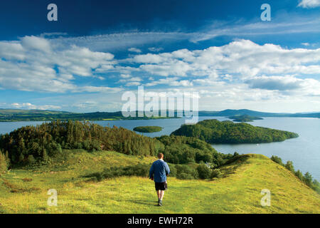 A walker descending from Conic Hill along Druim nam Buaraich, Loch Lomond and the Trossachs National Park - Stock Photo
