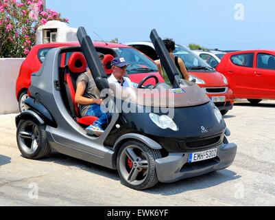 A car hire employee takes a tourist through the controls of a smart car. - Stock Photo
