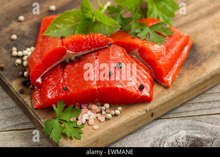 Top view shot of fresh bright red Copper River salmon fillets on cutting board, sea salt and herbs. - Stock Photo